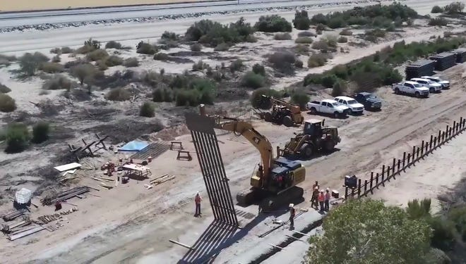 Aerial drone footage shows the installation of the first panel of 30-foot bollards west of Yuma, as part of a replacement project paid for using diverted military funds.