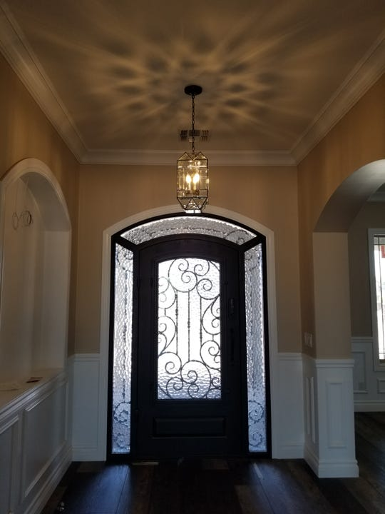 Beveled glass chandeliers throughout the home were crafted by Lori Plate's father. The effect in the foyer is stunning.