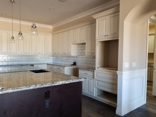 The kitchen provides an open sight line throughout the great room and is designed to be a family hub.