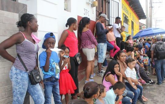 Migrantes aguardan mientras habitantes participan en una protesta para exigir la reubicación de un edificio de la Comisión Mexicana de Ayuda a Refugiados (Comar), una dependencia que brinda refugio a miles de migrantes en el sur de México, en Tapachula, Chiapas