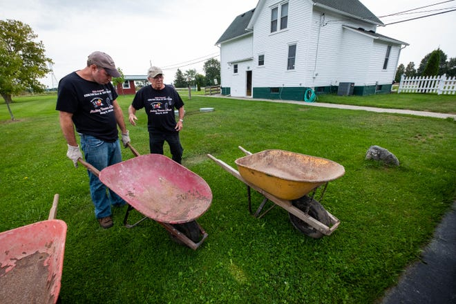Larry Collette, right, president of Special Dreams Farm in St. Clair, works with his son Greg on the farm Tuesday, Sept. 10, 2019. Greg, who is on the autism spectrum, is one of the many adults with special needs that operates the farm.