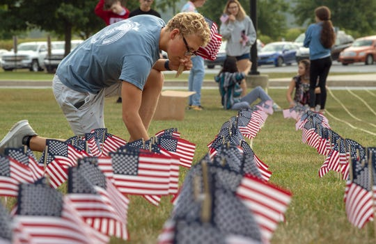 Clayton Brosend works with other students at Central York High School placing 2,977 flags Tuesday, the day before 9/11/