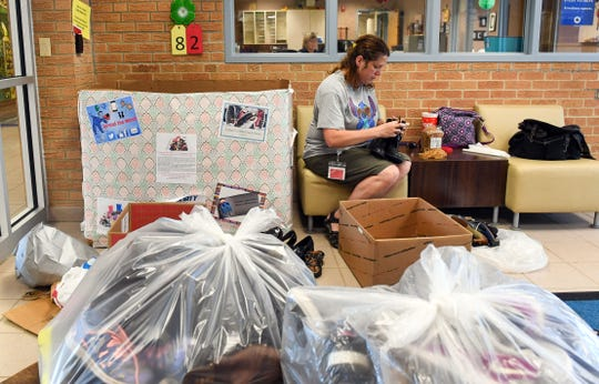 Donna Stolz, PTO fundraising coordinator, sorts through donated pairs of shoes as part of the third annual shoe drive Tuesday, September 10, at All City Elementary School.