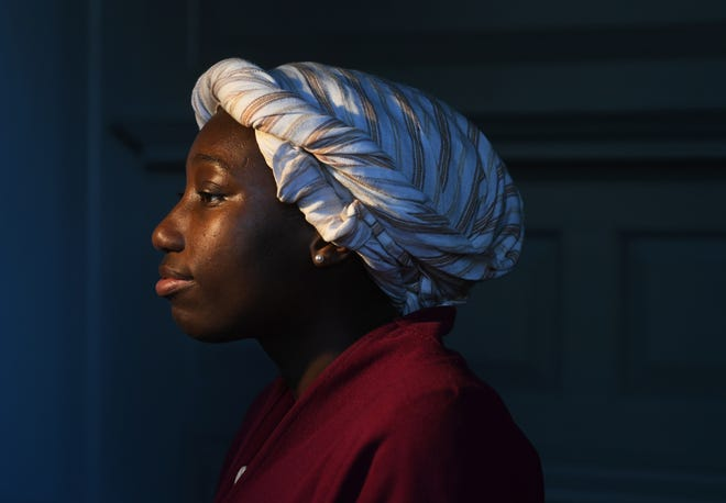 Da-Veia Brown, 24, gives tours while dressed in a period costume at Peyton Randolph House in Colonial Williamsburg in Williamsburg, Va.