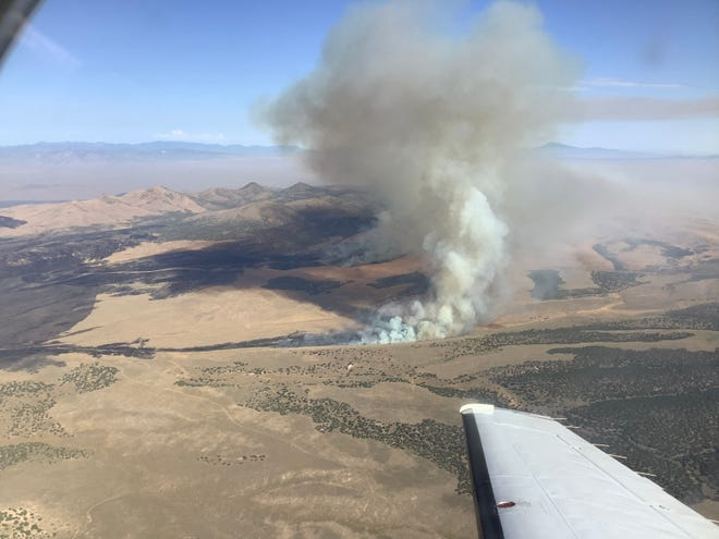 Rising smoke is seen from the window of an airplane flying above the Neck Fire, which started Thursday, Sept. 5, northwest of Cedar City.