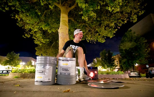 "In this Wednesday, Aug. 28, 2019 photo, Scott Schwarz smiles as a passerby dances while he performs along Center Street in downtown Provo, Utah. Schwarz has become a local celebrity known as ""The Road Drummer"" for his energetic street performances. (Isaac Hale/The Daily Herald via AP)"