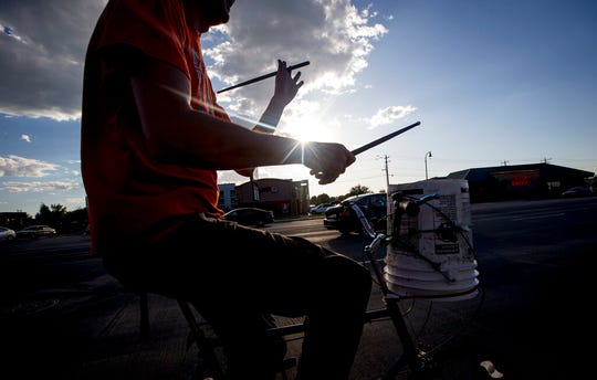 "In this Friday, Aug. 30, 2019 photo, Scott Schwarz twirls a drumstick as he drums a rhythm on a bucket while he bikes along State Street in Orem, Utah. Schwarz has become a local celebrity known as ""The Road Drummer"" for his energetic street performances. (Isaac Hale/The Daily Herald via AP)"
