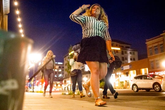 "In this Wednesday, Aug. 28, 2019 photo, Allie Jones, a senior at Brigham Young University, dances while she and her friends pass by Scott Schwarz as he performs at the intersection of Center Street and University Avenue  in downtown Provo, Utah. Schwarz has become a local celebrity known as ""The Road Drummer"" for his energetic street performances. (Isaac Hale/The Daily Herald via AP)"