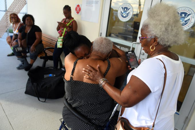 "Veronica Gibson (right) looks on as her sister Dorothy Buchanan, 73, cries and hugs fellow family members after being reunited in front of the U.S. Department of Homeland Security building Monday, Sept. 9, 2019, at the Treasure Coast International Airport and Business Park in Fort Pierce. Buchanan was one of about 20 Bahamians airlifted from Freeport, the main city on Grand Bahama, by Missionary Flights International and brought to Fort Pierce to meet friends and family. ""My sister almost drowned in the storm, but God had saved her and blessed her to be here,"" Gibson said. ""She needs assistance and to go to the hospital so we are planning to take her down to West Palm."" Freeport experienced major flooding due to storm surge as Hurricane Dorian sat over the Bahamas for several days."