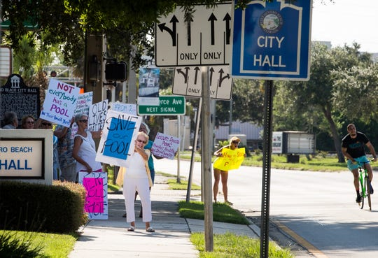 "June Vitti (left), of Vero Beach, holds a sign saying ""Save our Pool"" while advocating to keep the Leisure Square swimming pool open before the first public hearing about the Vero Beach budget Monday, Sept. 9, 2019, at City Hall."