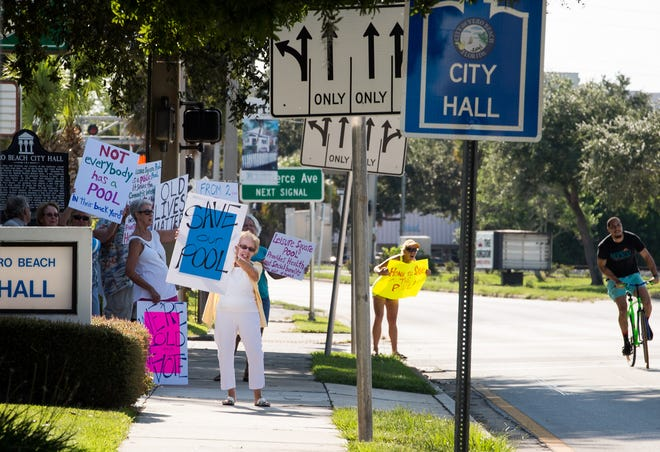 """Vero Beach City Council approved proposed fee increases for Leisure Square at its Monday meeting. City staff said the increases were to simplify the Leisure Square rate structure and to help narrow the gap between expenses and revenue there. In this photo, taken Monday, Sept. 9, 2019, at City Hall, June Vitti, left, of Vero Beach, holds a sign saying """"Save our Pool"""" while advocating to keep the Leisure Square swimming pool open."""