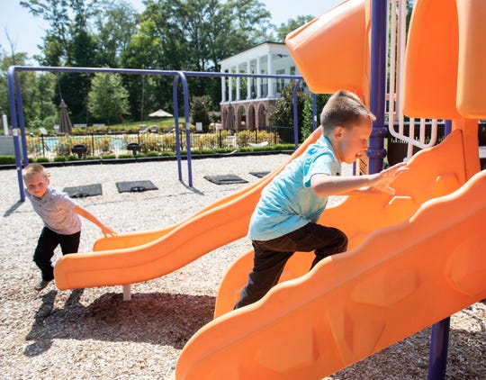 Colt Becker, 6, right, plays on a playground with his older brother Paxton, 8.