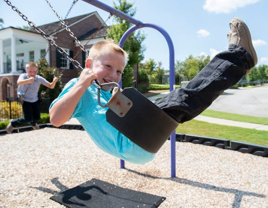 Colt Becker, 6, swings with his older brother Paxton, 8, on a swing set at a playground in their neighborhood.