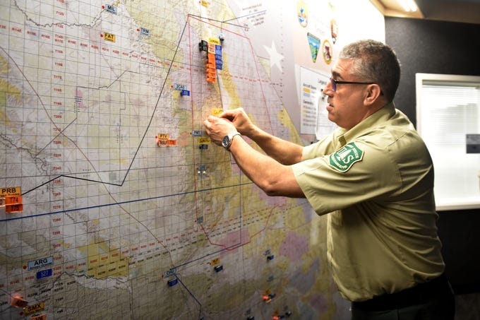 Manny Salas, a division chief with the U.S. Forest Service, posts a label onto a map at the Southern California Geographic Area Coordination Center, known as South Ops. The multi-agency group handles intelligence and coordination of major fires and disasters in Southern California and surrounding areas.