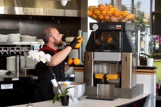Chef Kevin Kazem fills oranges in a large juicer at Vineyard Cafe in Oxnard's Topa Financial Plaza on Tuesday.