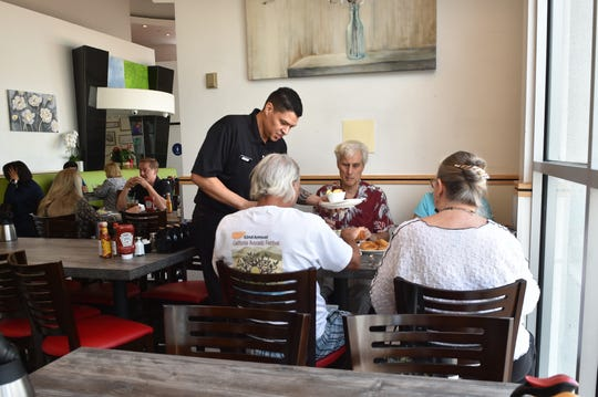 Jose Nunez delivers lunch to a group in the dining room of Vineyard Cafe at Oxnard's Topa Financial Plaza on Tuesday.