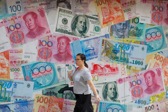 FILE - In this Aug. 6, 2019, file photo, a woman walks by a money exchange shop decorated with different countries currency banknotes at Central, a business district in Hong Kong. China's trade with the United States fell sharply in August as a tariff war that threatens global economic growth worsened.