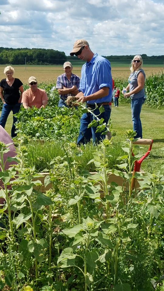 Adam Latsch, a Walworth County farmer, showed the variety of plants that are suitable for cover crops, indicating the differences and the benefits each contributes to building healthy soil.