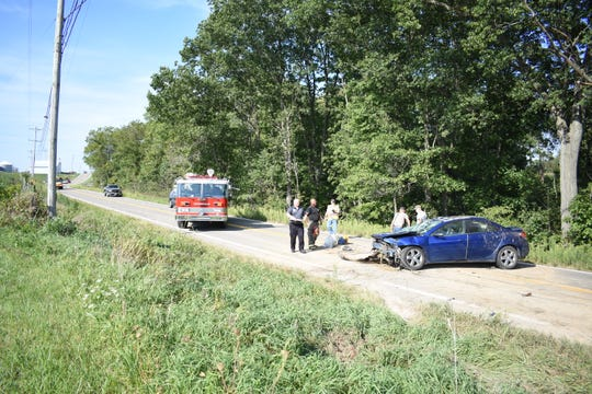 First responders work to clean the scene after a blue Pontiac G6 rolled over on Adamsville Road on Tuesday afternoon.