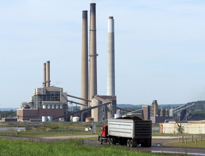 A coal truck heads toward AEP's Conesville power plant on Tuesday.  The coal mines that feed the plant will have to lay off much of its staff due to the plants closure next spring.