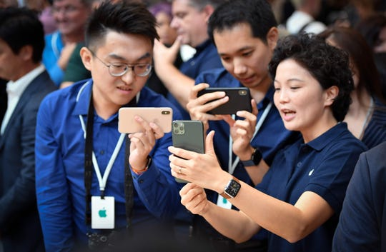 People try out a new Apple iPhone 11 Pro during an Apple product launch event at Apple's headquarters in Cupertino, California on September 10, 2019. - Apple unveiled its iPhone 11 models Tuesday, touting upgraded, ultra-wide cameras as it updated its popular smartphone lineup and cut its entry price to $699. (Photo by Josh Edelson / AFP)JOSH EDELSON/AFP/Getty Images ORG XMIT: Apple exp ORIG FILE ID: AFP_1K67HK