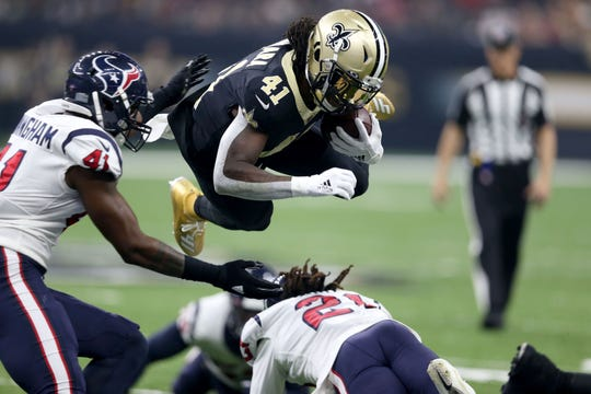 New Orleans Saints running back Alvin Kamara dives over Houston Texans cornerback Bradley Roby during the first quarter at the Mercedes-Benz Superdome in New Orleans.