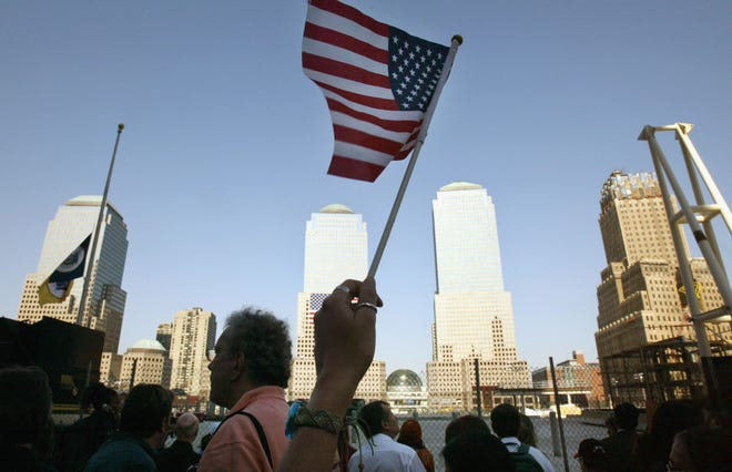 A woman waves an American flag to honor victims of the World Trade Center terrorist attacks during a memorial service at Ground Zero September 11, 2003 in New York City.