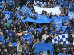 In this Dec. 9, 2011 file photo, supporters of Iranian soccer team Esteghlal, hold flags of their favorite team, at the Azadi (Freedom) stadium, in Tehran, Iran. Sahar Khodayari, an Iranian female soccer fan died after setting herself on fire outside a court after learning she may have to serve a six-month sentence for trying to enter a soccer stadium where women are banned, a semi-official news agency reported Tuesday, Sept. 10, 2019.