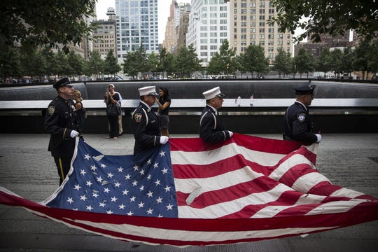 New York City police officers, firefighters and Port Authority workers participate in a memorial at the former site of the World Trade Center on Sept. 11, 2014.