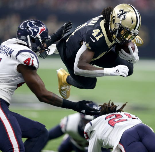 Saints running back Alvin Kamara dives over Texans cornerback Bradley Roby (21) during the first quarter at the Mercedes-Benz Superdome.