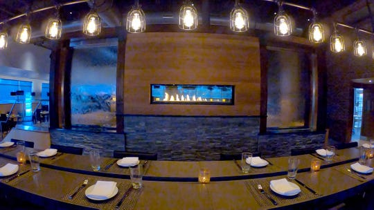 The communal table and cascading water wall inside The Edge in Jackson.