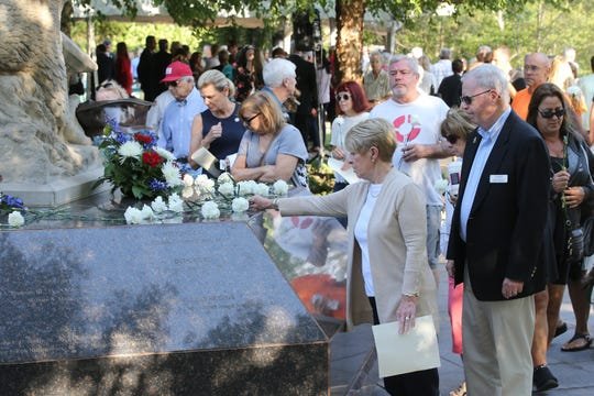 Guests place flowers on the memorial during Monmouth County's 9/11 Memorial Ceremony in Atlantic Highlands, NJ Wednesday, September 11, 2019.
