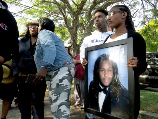 Jehadje J. McMillian's brother Nyree Jennings, 16, and sister Aniyah Mcleod, 17, hold his photo outside St. Stephen's Church on Springwood Avenue in Asbury Park Wednesday, September 11, 2019.   McMillan's mother Nikkia Jennings-Fitzpatrick is at left.  The prosecutor announced that four men were arrested on charges related to McMillian's death.