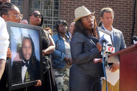 Aniyah Mcleod, 17, holds a photo of her murdered brother Jehadje J. McMillian while her mother Nikkia Jennings-Fitzpatrick speaks during a news conference outside St. Stephen's Church on Springwood Avenue in Asbury Park Wednesday, September 11, 2019.   Monmouth County Prosecutor Christopher J. Gramiccioni (right) announced that four men were arrested on charges related to McMillian's death.