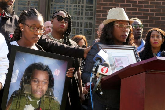 Aniyah Mcleod, 17, holds a photo of her murdered brother Jehadje J. McMillian while her mother Nikkia Jennings-Fitzpatrick speaks during a news conference outside St. Stephen's Church on Springwood Avenue in Asbury Park Wednesday, September 11, 2019.  The Monmouth County Prosecutor announced that four men were arrested on charges related to McMillian's death.
