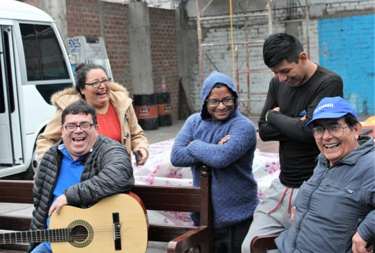 Javier Ochoa, with guitar and pastor of two Methodist churches, joins a bus driver named Danny (blue hoodie), Luis Ruiz, right, and others in a hearty laugh during a farewell service for a mission group from Abilene.