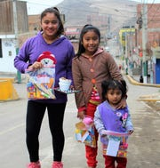 Three girls head home with gifts of school supplies after a vacation Bible school at a Methodist church in Ventanilla district of Callao near Lima, Peru.