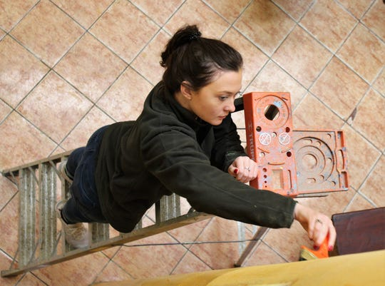 Arabella Jackson reaches to paint inside the sanctuary of a Methodist church in Ventanilla district of Callao, Peru. She is a former student at McMurry University in Abilene.