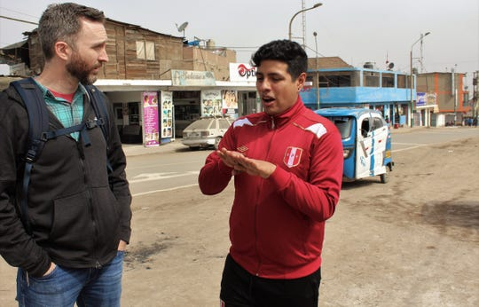 Joseph Carrillo, right, explains to Abilenian Tyson Alexander how it is in Peru during a walk to a market in the district of Ventanilla. A mission group from Aldersgate UMC were stunned by the low price of fresh fruit.