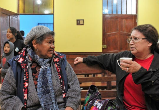 Hope Sandoval, a teacher at Cooper High School, right, speaks in Spanish with Susana Grados inside a Methodist church in the Ventanilla district of Callao, near Lima, Peru.