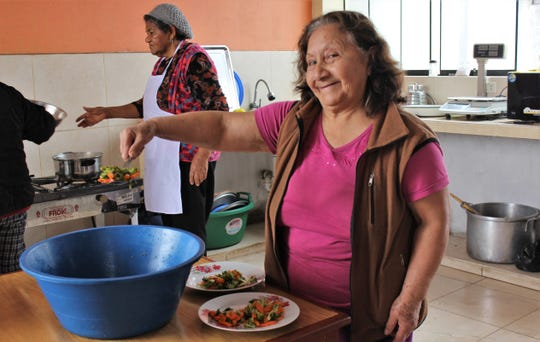 Maria Cabanillas, pastor of a small Methodist church in Ventanilla, a district of Calloa, fills plates with vegetables for lunch in the kitchen that's above and to the next the sanctuary. Aug. 5 2019