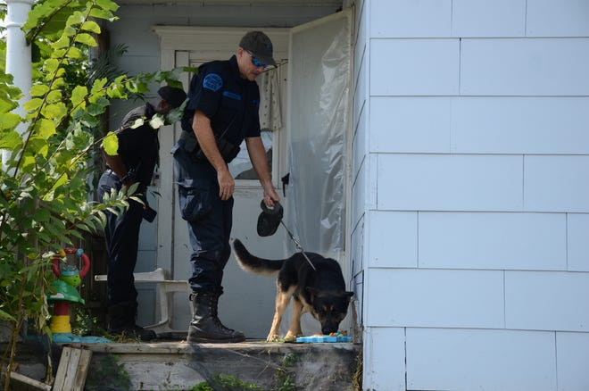 Michigan State Police Trooper Joel Service and his dog Baki search the porch at 17 Wabash Ave. on Wednesday looking for evidence in the Tuesday morning fire.