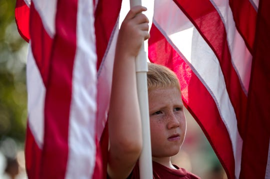 Jesse Lewis, 7, carries a flag next to his siblings Kurtis and Elizabeth Lewis during a 9/11 remembrance ceremony on Wednesday, Sept. 11, 2019 at McCamly Park in Battle Creek, Mich. The Yellow Ribbon Committee and several other sponsors organized the event to commemorate the first responders who gave their service that day, and for many, their lives.