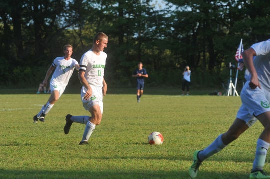 Clear Fork's Isaac Kistler dribbles the ball with teammate Seth Stoner in the background shouting advice.