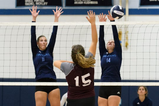 MMU's Elana Philbrick (11) and Natalie Malmgren (14) try to block the shot by Lyndon's Rio Steen (15) during the high school girls volleyball match between Lyndon Institute and Mount Mansfield on Wednesday afternoon September 11, 2019 in Jericho, Vermont.