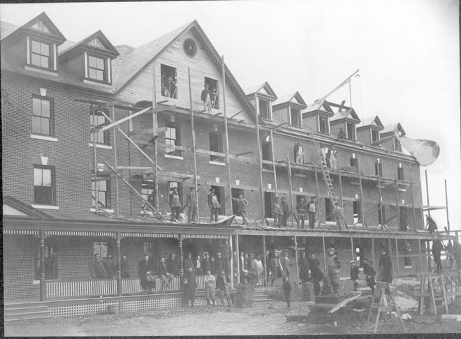 1907: Workmen apply a brick facade to Founders Hall at St. Michael's College in Colchester.
