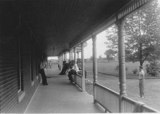 1931: Students lounge along the main, southern entrance to Founders Hall at St. Michael's College in Colchester. The long, covered porch — original to the building — was removed in 1953.