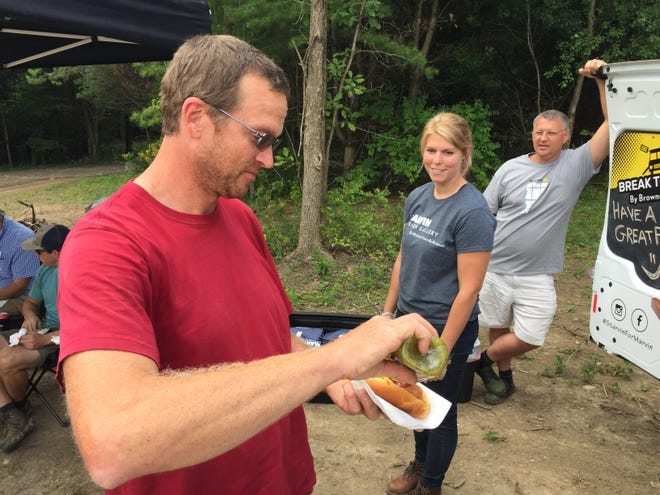 Cory Glover, a carpenter with Reiss Building and Renovation, prepares to eat a hot dog provided by the Break Time By Brownell van as Brownell employees Jackie Turtur and Charles Pelsue look on in Monkton on Sept. 6, 2019.