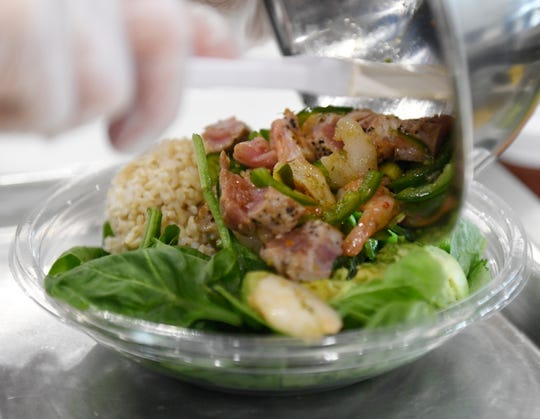 A seared tuna poke bowl is made, Wednesday, Sept. 11, 2019, at Hana Poke. The restaurant offers cooked proteins, such as chicken and steak, as well as the traditional raw, seafood options.