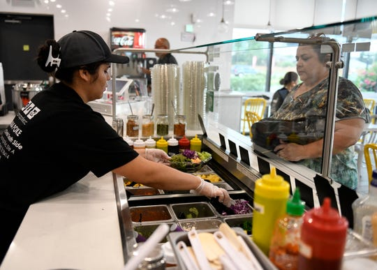 Tehani Samson builds a poke bowl for a customer, Wednesday, Sept. 11, 2019. Poke is a Hawaiian dish that is traditionally a bowl of rice with raw seafood, such as tuna or salmon, on top with various toppings, such as sesame seeds, soy sauce, avocado slices, etc.